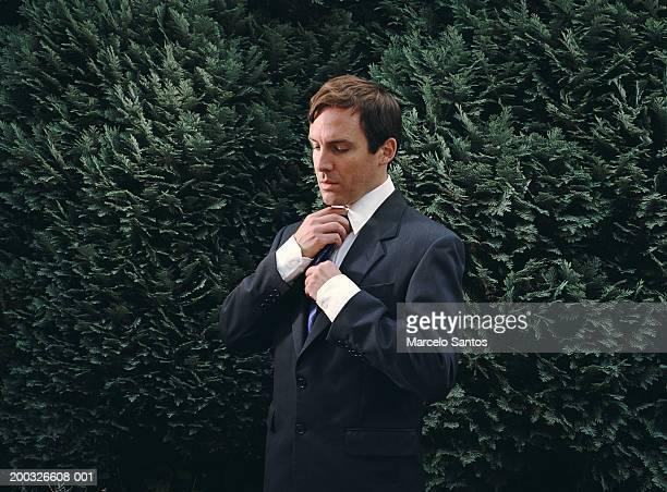 Businessman adjusting tie by hedge