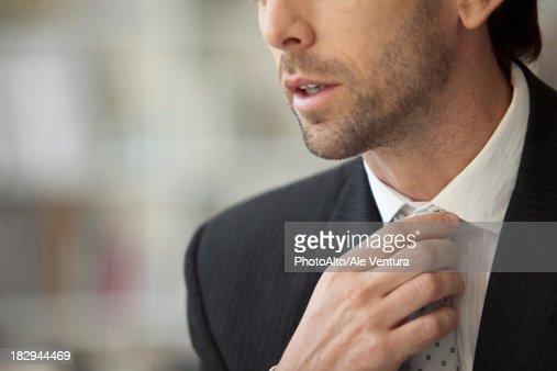 Businessman adjusting tie, cropped