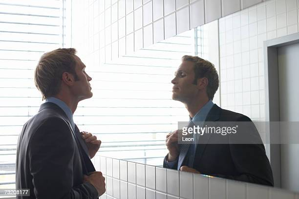Businessman adjusting tie in bathroom mirror
