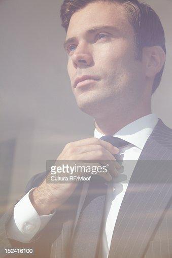 Businessman adjusting tie in window