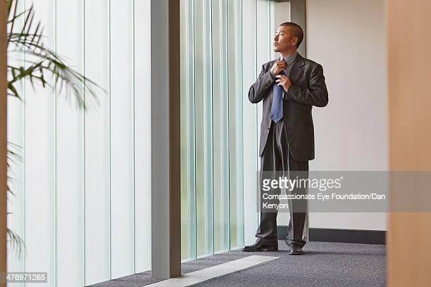 Businessman adjusting tie looking out of window
