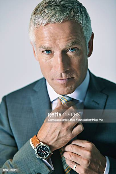 Businessman adjusting tie, portrait