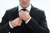 Businessman adjusting tie, Stockholm, Sweden
