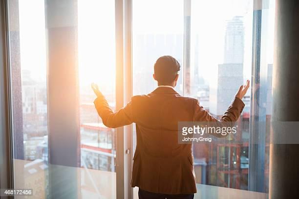 Homme d'affaires en admirant la ville à travers la fenêtre et le coucher de soleil