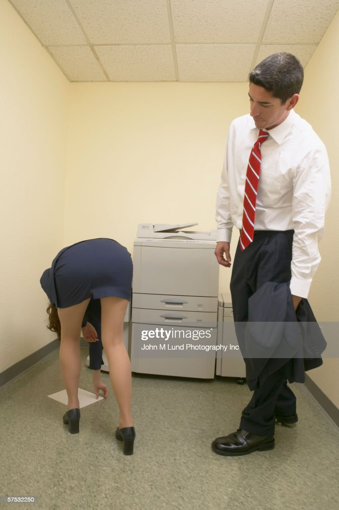Businessman admiring female colleague?s buttocks as she bends over : Stock Photo