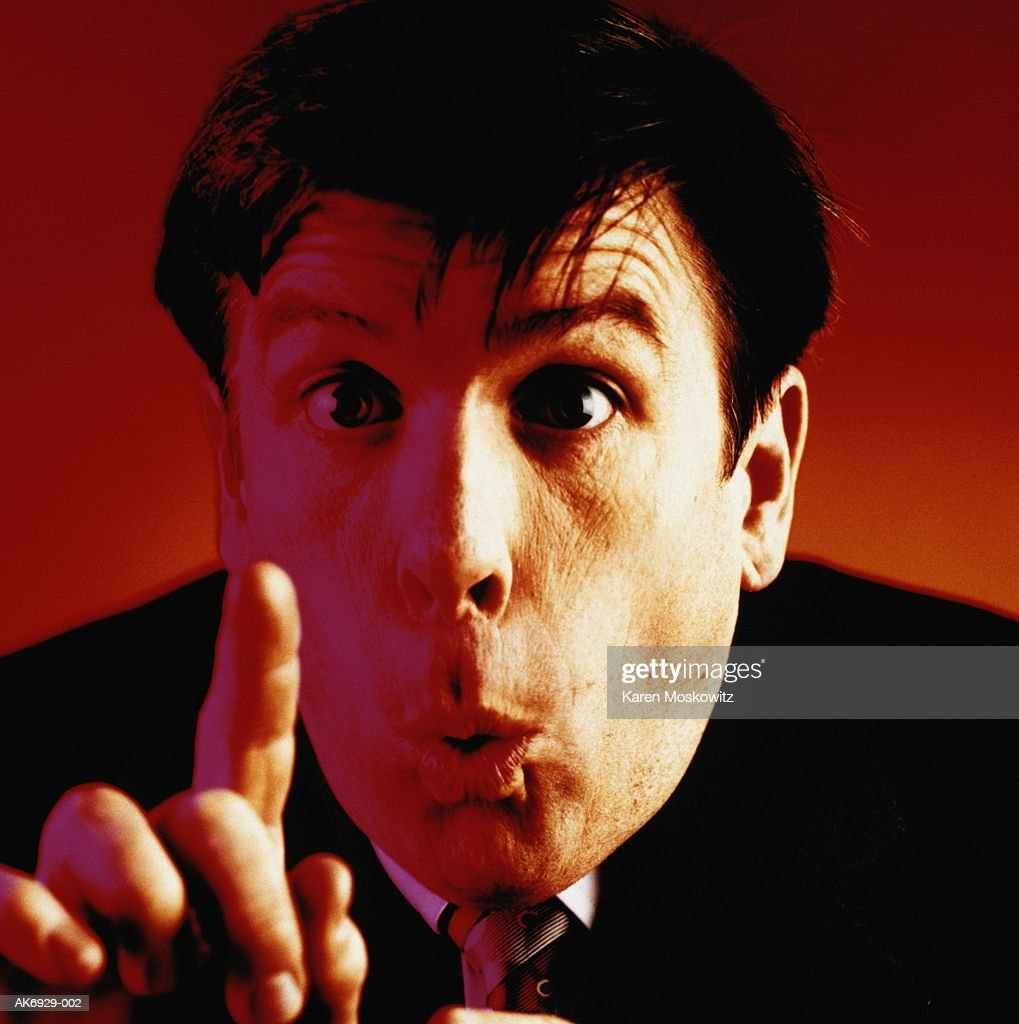 Businessman against red background raising finger, close-up : Stock Photo