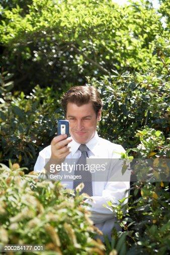 Businessman amongst bushes, holding up mobile phone, smiling : Stock Photo