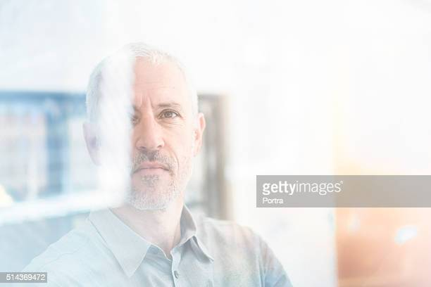 Businessman analysing graph on glass wall