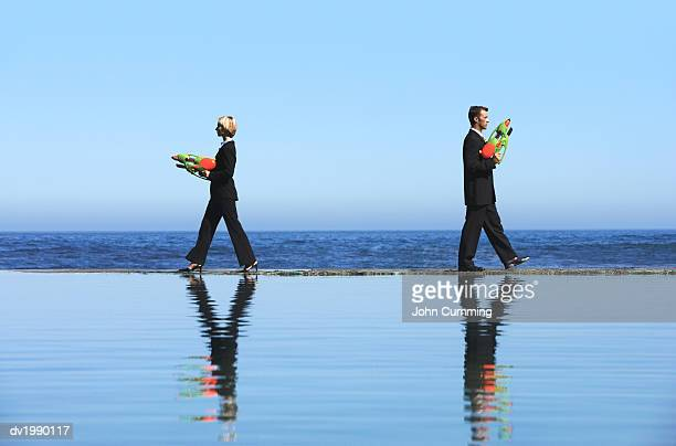 Businessman and a Businesswoman Dueling With Water Pistols by the Sea