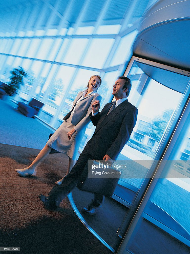Businessman and a Businesswoman Entering an Office Lobby Through a Revolving Door : Stock Photo