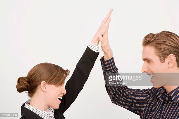Businessman and a businesswoman giving high-five and smiling