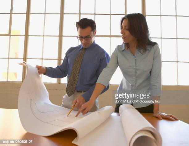Businessman and a businesswoman looking at a blueprint in an office