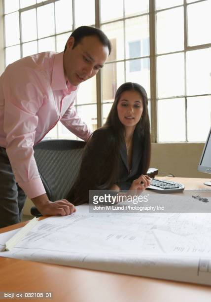 Businessman and a businesswoman looking at a blueprint
