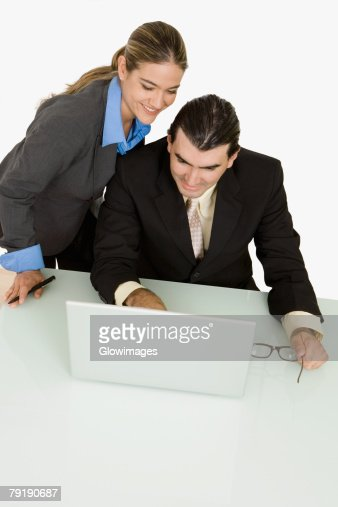 Businessman and a businesswoman using a laptop and smiling : Stock Photo