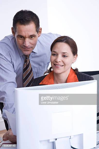Businessman and businesswoman at a meeting in front of a laptop