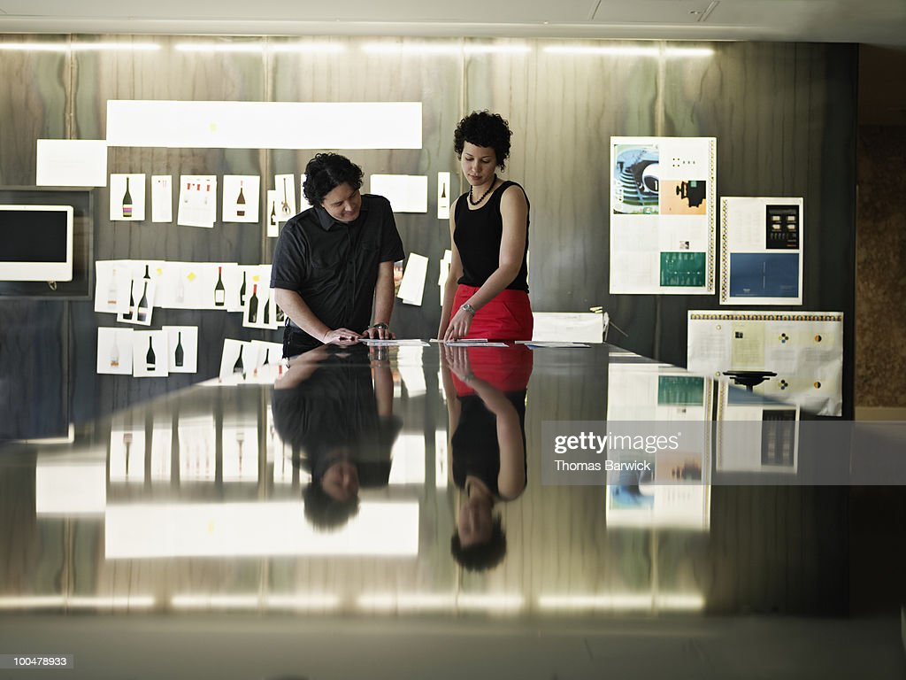 Businessman and businesswoman examining documents : Stock Photo
