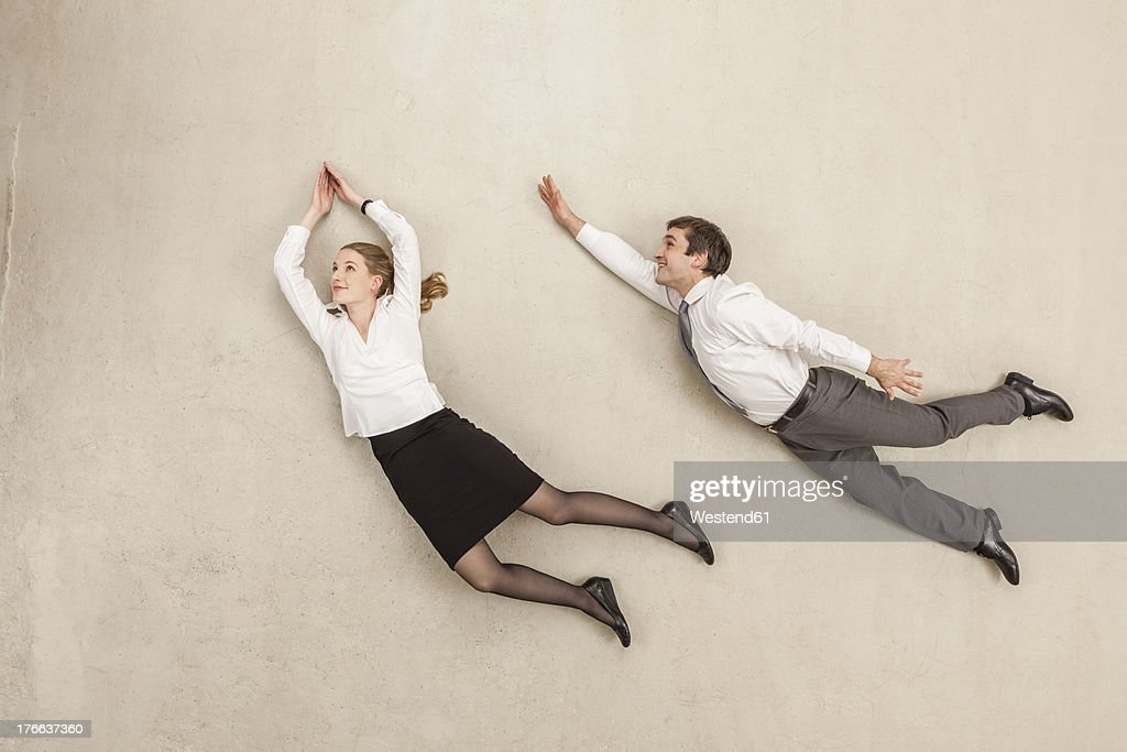 Businessman and businesswoman flying against beige background : Stock Photo
