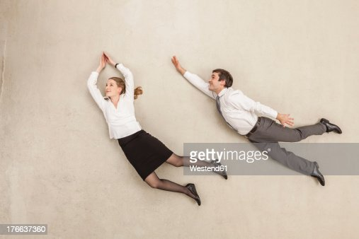 Businessman and businesswoman flying against beige background