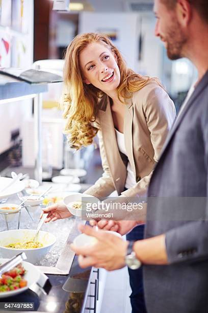 Businessman and businesswoman having buffet breakfast