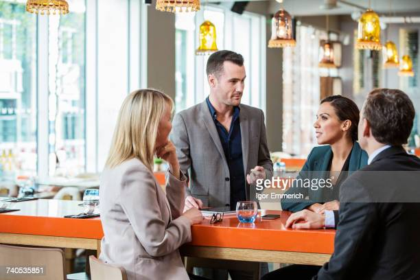 Businessman and businesswoman in discussion in cafe