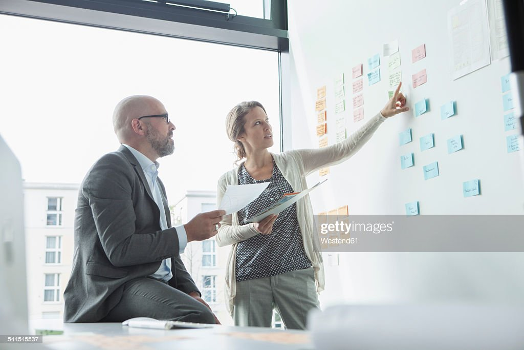 Businessman and businesswoman in office at wall with adhesive notes