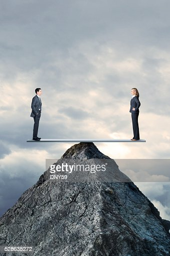 Businessman And Businesswoman In Perfect Balcance On Seesaw On MountaintopBusinessman And Businesswoman