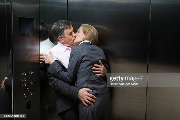 Businessman and businesswoman kissing in elevator