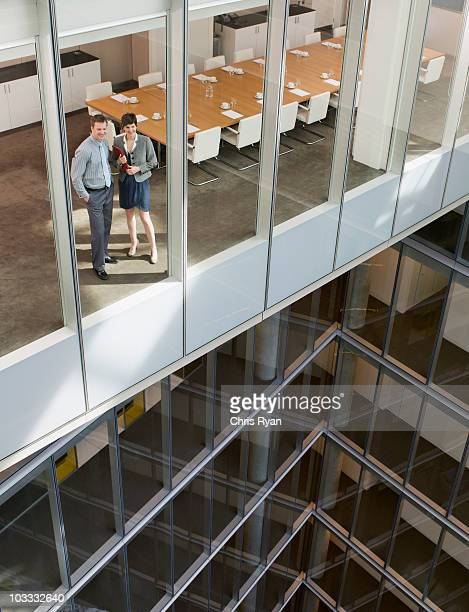 Businessman and businesswoman looking out conference room window