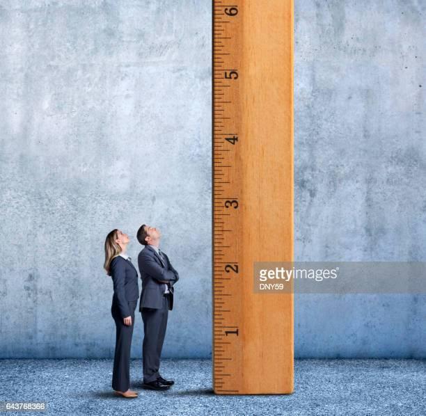 Affärsmannen och affärskvinna tittar upp en lång stege