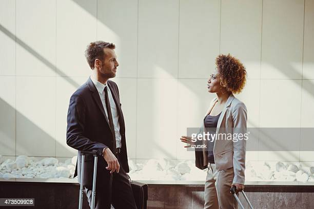 Businessman and businesswoman on business travel in hotel hall