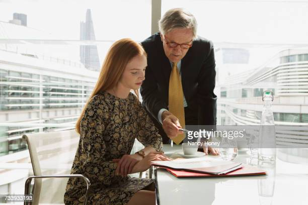 Businessman and businesswoman reading and analysing report, London, UK