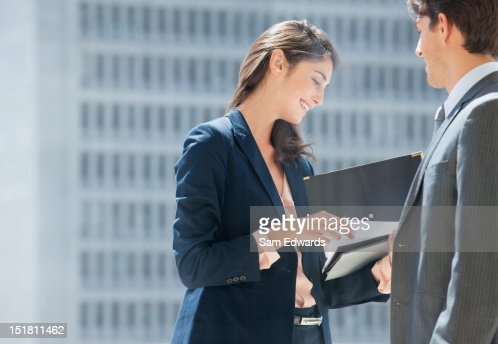 Businessman and businesswoman reviewing paperwork on urban balcony : Stock Photo
