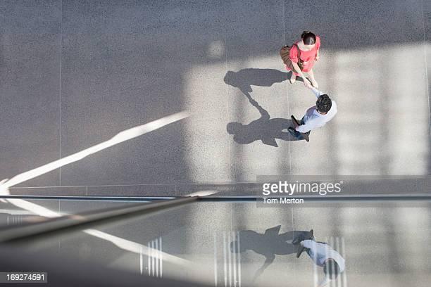 Businessman and businesswoman shaking hand on sidewalk