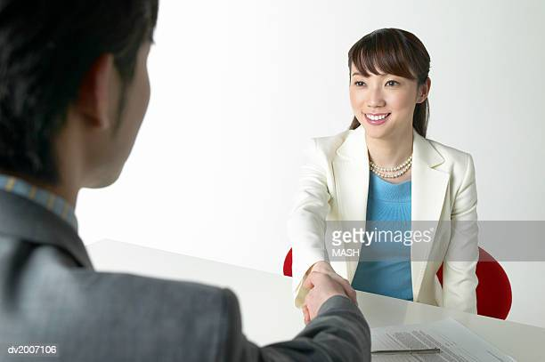 Businessman and Businesswoman Shaking Hands Across a Table