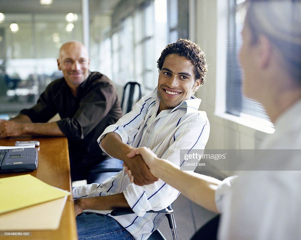 Businessman and businesswoman shaking hands at conference table