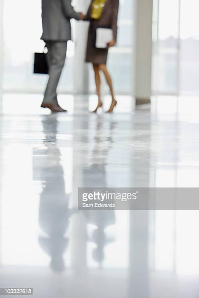 Homme d'affaires et Femme d'affaires se serrant la main dans le hall