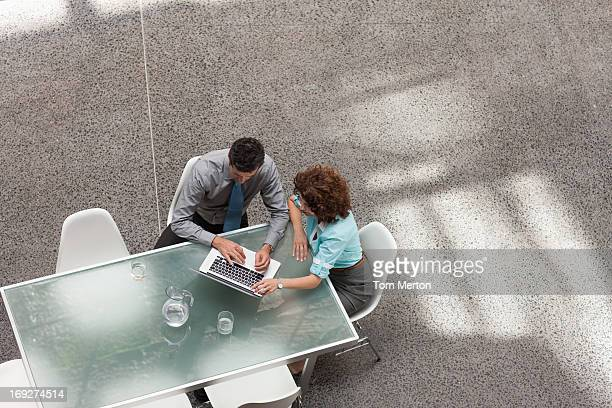 Businessman and businesswoman sharing laptop at table