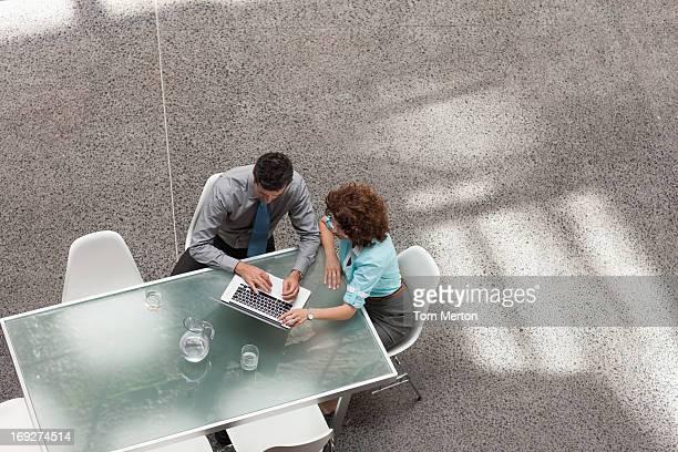 Geschäftsmann und Geschäftsfrau in laptop am Tisch