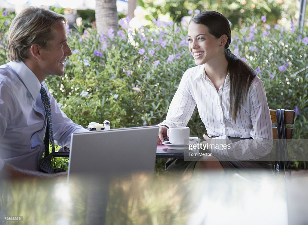 Businessman and businesswoman sitting at a patio table with laptop : Stock Photo