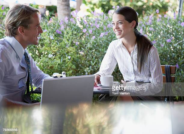 Businessman and businesswoman sitting at a patio table with laptop
