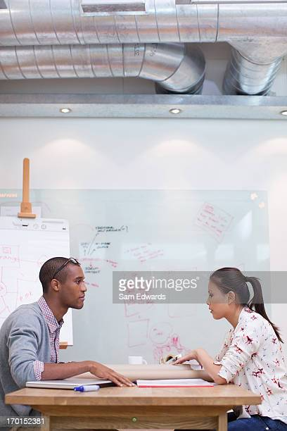 Businessman and businesswoman sitting face to face in meeting