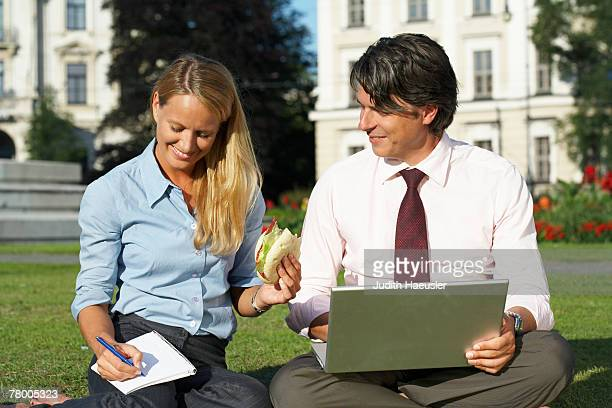 Businessman and businesswoman sitting in field working together.