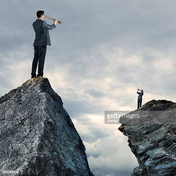 Businessman and Businesswoman Standing On Mountaintops Looking Through Spyglass