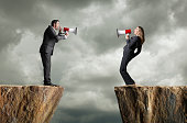 A businessman and a businesswoman standing on opposite cliffs shout at each other through their megaphones.