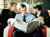 Businessman and businesswoman talking behind man reading newspaper