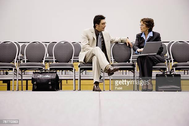 Businessman and Businesswoman Talking in Auditorium