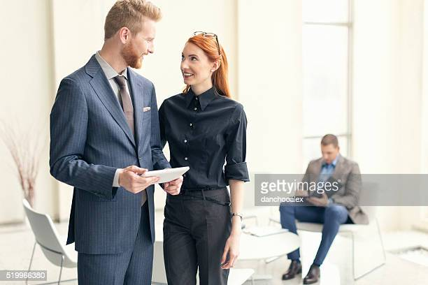 Businessman and businesswoman talking in the lobby