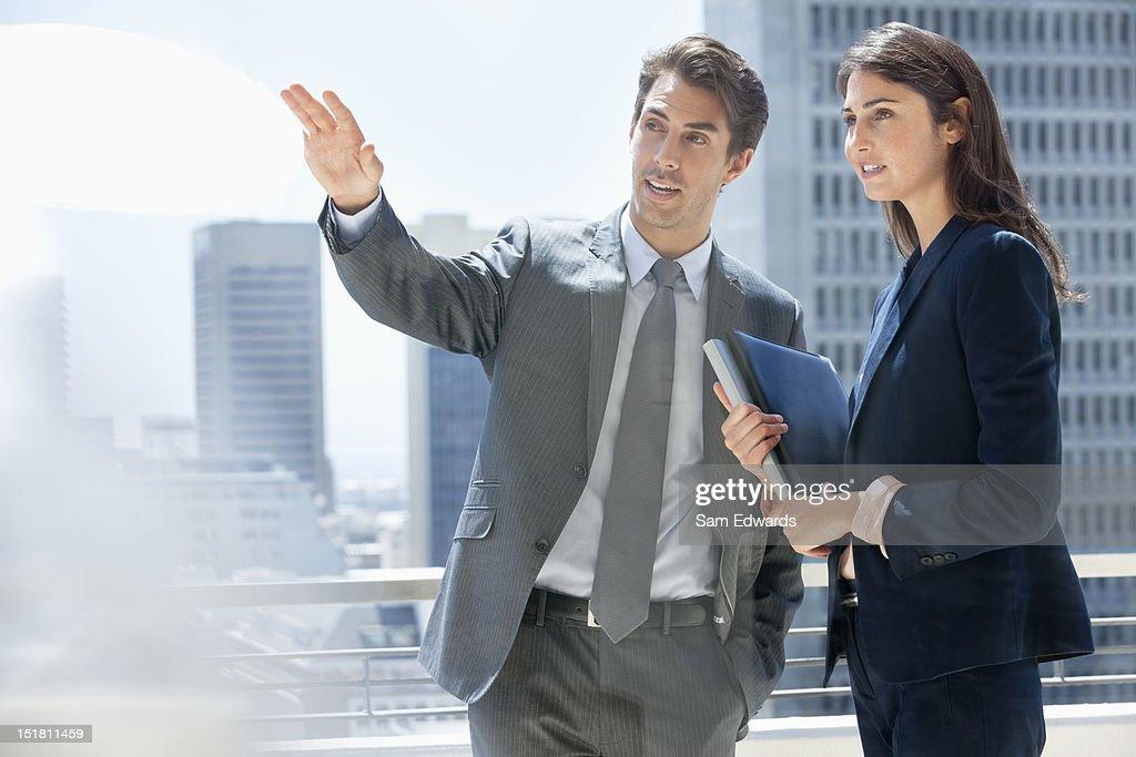 Businessman and businesswoman talking on urban balcony