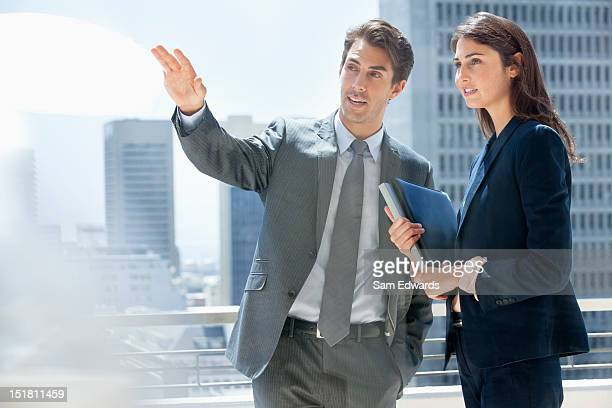 Businessman and businesswoman talking on urban balcony