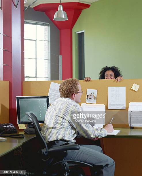 Businessman and businesswoman talking to each other over cubicle wall
